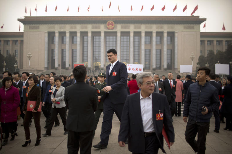 FILE - In this March 14, 2018, file photo, former NBA basketball player Yao Ming, center, a delegate to the Chinese People's Political Consultative Conference (CPPCC), leaves after a plenary session of the CPPCC at the Great Hall of the People in Beijing. Yao is now president of the Chinese Basketball Association, which announced over the weekend it is suspending its ties with the Rockets in retaliation for Houston Rockets general manager Daryl Morey's tweet that showed support for Hong Kong anti-government protesters. (AP Photo/Mark Schiefelbein, File)