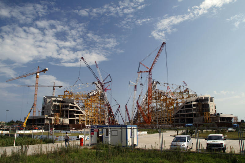 In this photo taken Thursday, Aug. 9, 2012, hoisting cranes surround the Olympic Stadium at the Olympic Park which is under construction in the Black Sea resort of Sochi, southern Russia. Sochi will host the 2014 Winter Olympics. The idea of holding the Winter Olympics in Sochi once seemed as much of a long shot as a gold medal for Jamaica's bobsledders — a city that few outside Russia had ever heard of, in a country notorious for inefficient construction, corruption, and a byzantine visa regime. (AP Photo/Igor Yakunin)