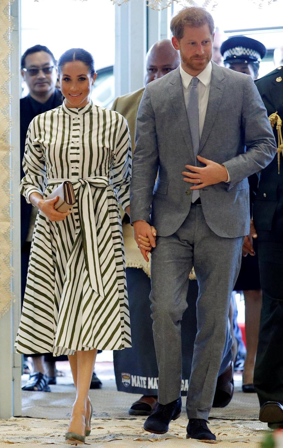 <p>On October 26, the Duke and Duchess of Sussex met with Tonga Prime Minister Akilisi Pohiva. For the occasion, Meghan dressed in a striped midi dress by Martin Grant – a label she has looked to throughout the tour. She accessorised the daytime look with a Prada clutch, stud earrings from Birks and olive green shoes. <em>[Photo: Getty]</em> </p>