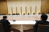 Japanese Prime Minister Yoshihide Suga, center, declares a state of emergency for Tokyo and three other prefectures during the government task force meeting for the COVID-19 measures at the prime minister's office Friday, April 23, 2021, in Tokyo. (AP Photo/Eugene Hoshiko, Pool)