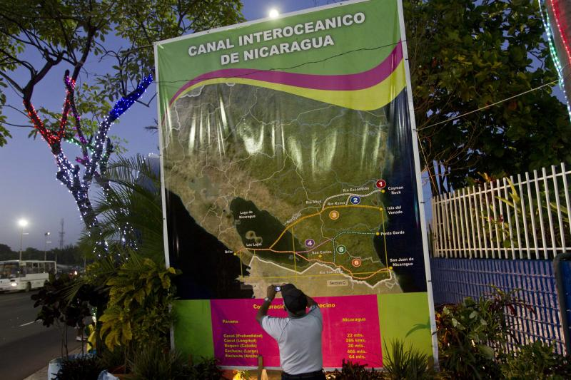 In this Dec. 4, 2013 photo, Oscar Torres, a 62-year-old retired construction worker takes photos of a banner showing a map of Nicaragua with possible routes of the Inter-Oceanic canal in Managua, Nicaragua. Six months after the Sandinista government granted a Chinese businessman a 100-year concession to build a vast canal across the country, Nicaraguans are confident the $40 billion canal will become reality, lifting their country from poverty to prosperity. (AP Photo/Esteban Felix)