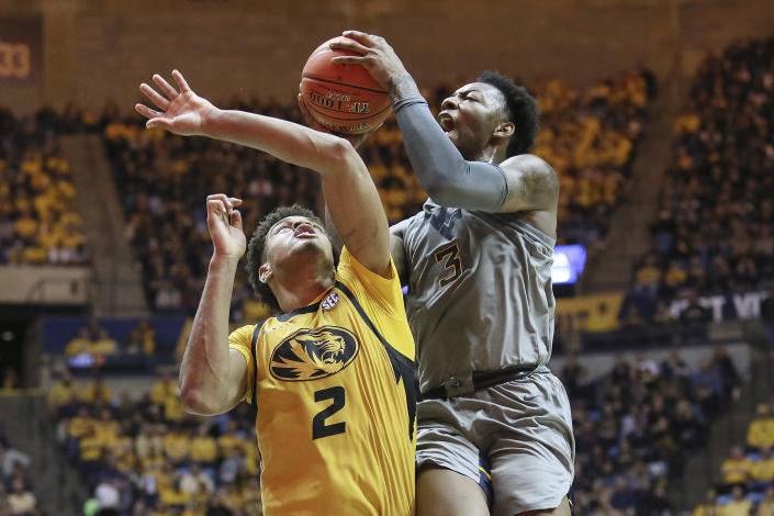 West Virginia forward Gabe Osabuohien (3) goes to make a shot as he is defended by Missouri forward Tray Jackson (2) during the second half of an NCAA college basketball game Saturday, Jan. 25, 2020, in Morgantown, W.Va. (AP Photo/Kathleen Batten)