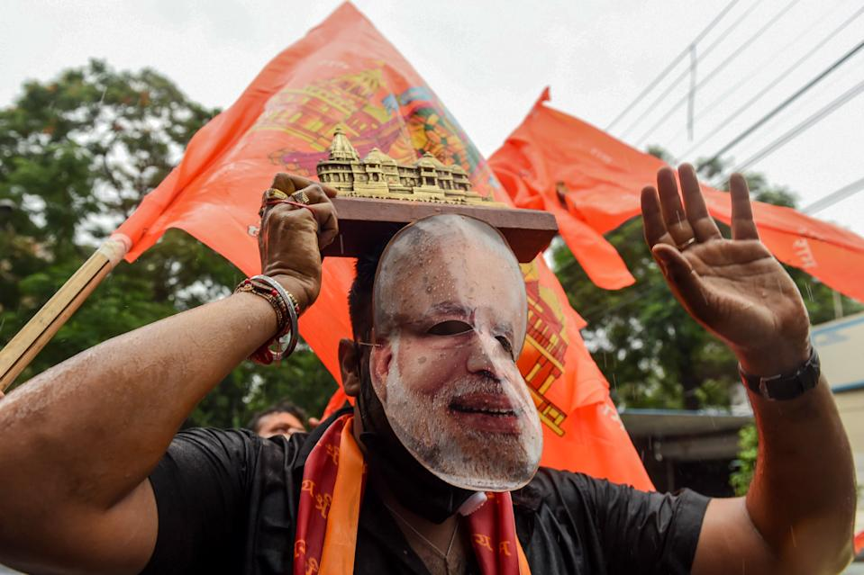 A Bharatiya Janata Party (BJP) supporter wearing a mask of India's Prime Minister Narendra Modi celebrates with others before the groundbreaking ceremony of the Ram Temple in Ayodhaya, in New Delhi on August 5, 2020. - India's Prime Minister Narendra Modi will lay the foundation stone for a grand Hindu temple in a highly anticipated ceremony on August 5 at a holy site that was bitterly contested by Muslims, officials said. The Supreme Court ruled in November 2019 that a temple could be built in Ayodhya, where Hindu zealots demolished a 460-year-old mosque in 1992. (Photo by Money SHARMA / AFP) (Photo by MONEY SHARMA/AFP via Getty Images)