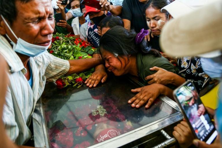 The wife of Phoe Chit, a protester who died during a demonstration against the military coup, cries over the coffin of her husband during his funeral in Yangon on March 5, 2021