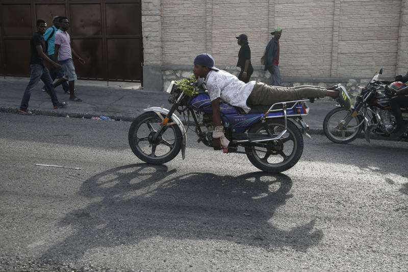 A man rides his motorcycle with no hands as protestors advance toward Petionville after marching past United Nations headquarters, in Port-au-Prince, Haiti, Friday, Oct. 4, 2019. Thousands of protesters marched through the Haitian capital to the U.N. headquarters Friday in one of the largest demonstrations in a weekslong push to oust the embattled President Jovenel Moise. (AP Photo/Rebecca Blackwell)