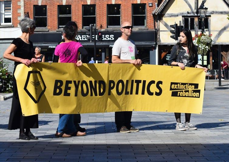 Four activists hold a banner reading 'Beyond Politics - Extinction Rebellion' in a town square.