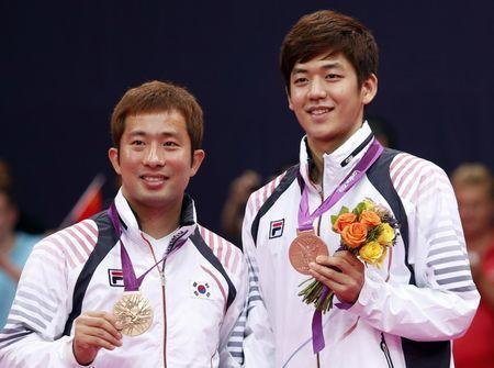 FILE PHOTO: Bronze medallists South Korea's Lee Yong-dae (R) and Chung Jae-sung pose at the men's doubles badminton victory ceremony during the London 2012 Olympic Games at the Wembley Arena August 5, 2012. REUTERS/Bazuki Muhammad