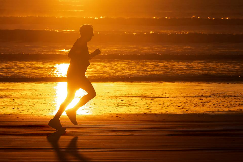 An elderly man jogs at empty New Brighton beach in Christchurch, New Zealand.