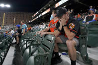 Donnie Carroll, right, reacts after his childhood friend, Baltimore Orioles starting pitcher Bruce Zimmermann gave up a solo home run to Boston Red Sox's Rafael Devers to break a 2-2 tie during the sixth inning of a baseball game, Saturday, April 10, 2021, in Baltimore. (AP Photo/Julio Cortez)