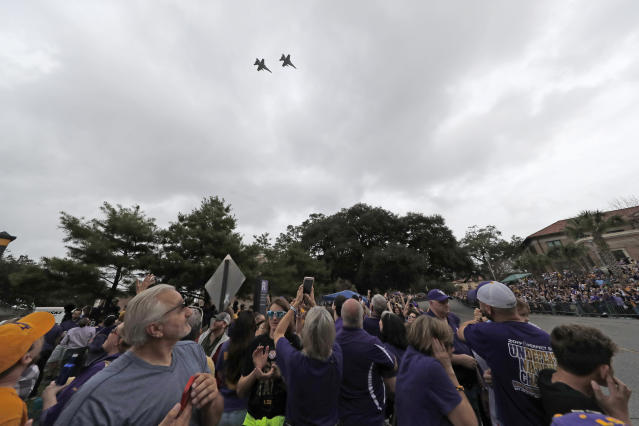 Fighter jets fly in formation overhead as fans wait for the start of a parade celebrating LSU's NCAA college football championship, Saturday, Jan. 18, 2020, on the LSU campus in Baton Rouge, La. (AP Photo/Gerald Herbert)