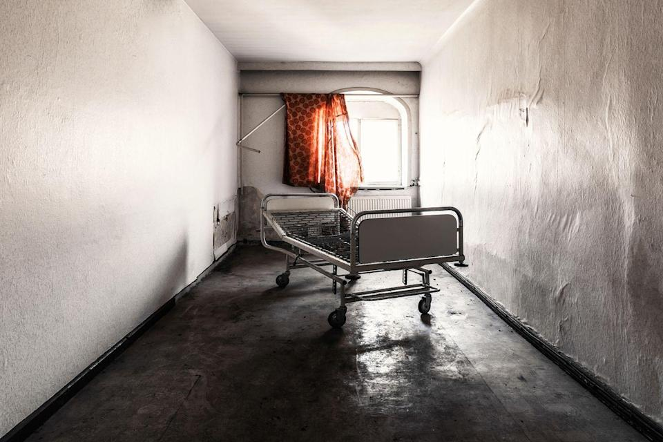 <p>A lone gurney left behind in a cold and empty hospital room.</p>