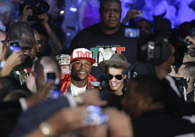 Floyd Mayweather Jr., center left, is joined by Justin Bieber as he enters the area for his WBC-WBA welterweight title boxing fight against Marcos Maidana Saturday, May 3, 2014, in Las Vegas. (AP Photo/Isaac Brekken)
