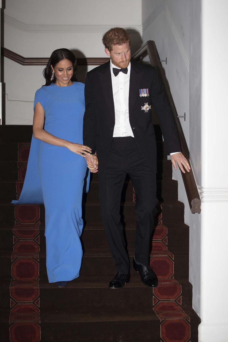 """<p>Stepping out for a black tie dinner at the Grand Pacific Hotel on Tuesday night, Meghan opted for the Ginkgo cape dress by London-based brand <a href=""""https://www.safiyaa.com/collections/dresses/products/ginkgo-cape-dress"""" rel=""""nofollow noopener"""" target=""""_blank"""" data-ylk=""""slk:Safiyaa"""" class=""""link rapid-noclick-resp"""">Safiyaa</a>. </p><p>Kensington Palace confirmed that the jewels were 'borrowed' and as royal correspondent <a href=""""https://twitter.com/byEmilyAndrews/status/1054663599749181440"""" rel=""""nofollow noopener"""" target=""""_blank"""" data-ylk=""""slk:Emily Andrews notes"""" class=""""link rapid-noclick-resp"""">Emily Andrews notes</a> it's most likely that they were lent to her by the Queen, who visited the same hotel on her 1953 royal tour.</p>"""