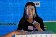 A woman wearing a face shield votes in the provincial election in Nonthaburi, Thailand