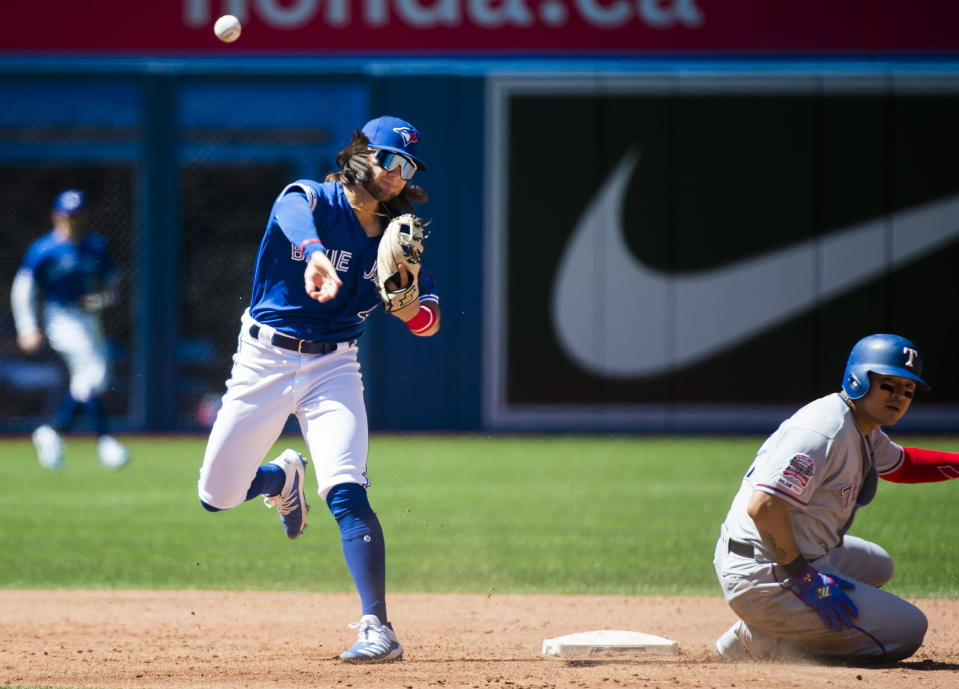 Toronto Blue Jays shortstop Bo Bichette (11) forces out Texas Rangers designated hitter Shin-Soo Choo (17) at second base but does not turn over the double play in time during the sixth inning of a baseball game, Wednesday Aug. 14, 2019 in Toronto.(Nathan Denette/The Canadian Press via AP)