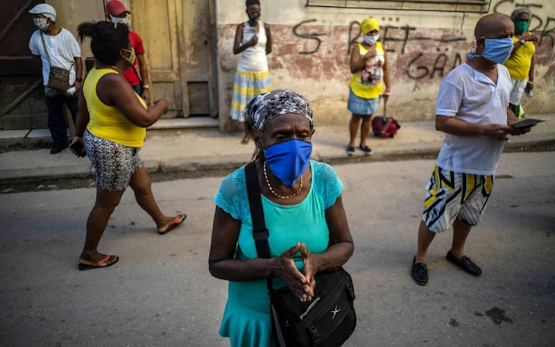 People wearing face masks pray during a Catholic Mass broadcast by radio in honor of the Virgin of Charity of Cobre, on her feast day in Havana, Cuba - AP