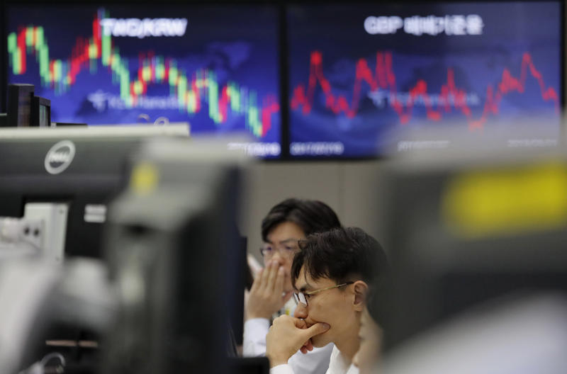 In this Aug. 1, 2019, photo, currency traders watch monitors at the foreign exchange dealing room of the KEB Hana Bank headquarters in Seoul, South Korea. Asian shares were mostly higher Wednesday, Aug. 14, 2019, after the U.S. said it would hold off on tariffs of Chinese imports of mobile phones, toys and several other items typically on holiday shopping lists. (AP Photo/Ahn Young-joon)