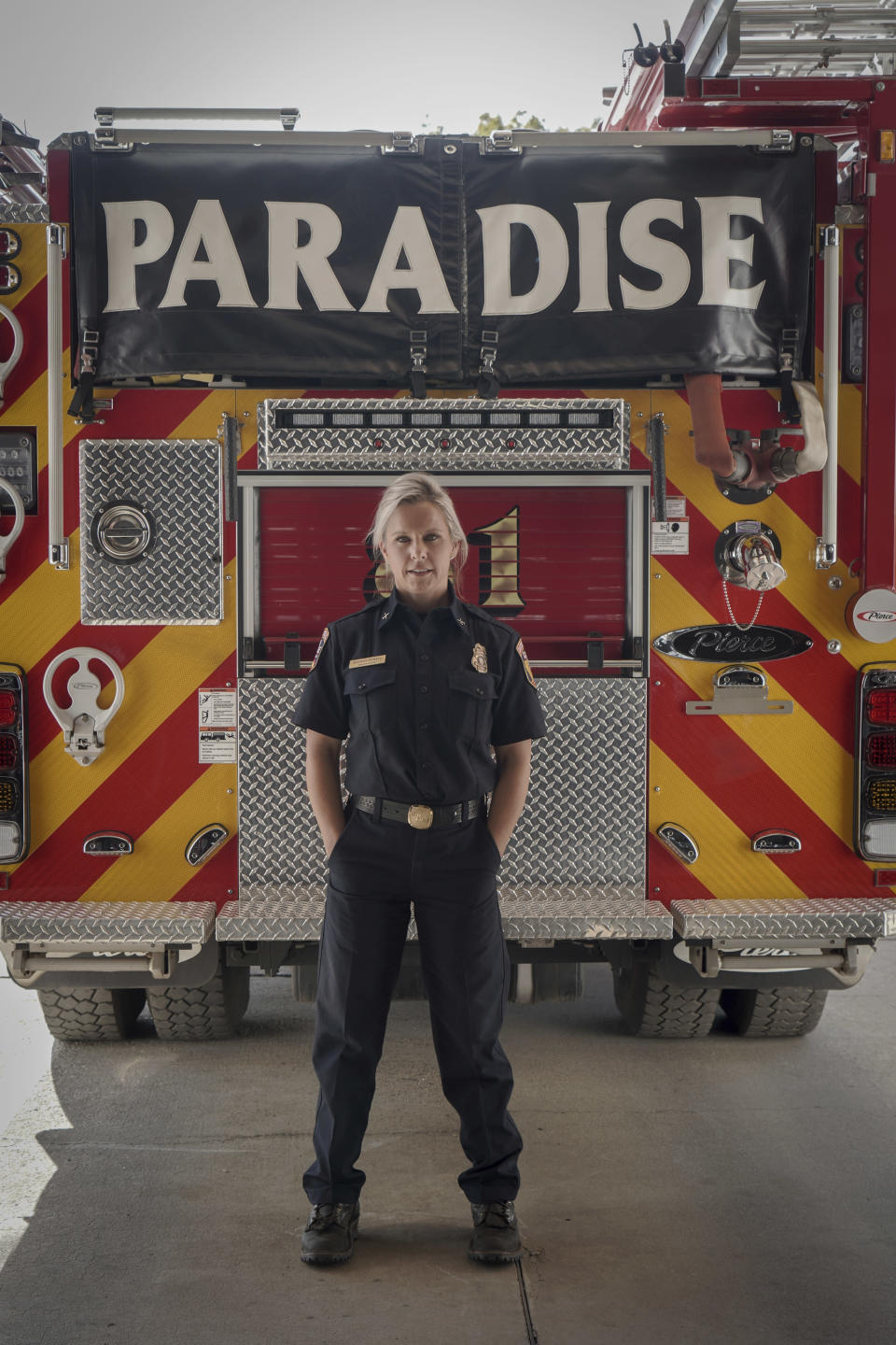 """This image released by National Geographic shows firefighter Shawna Powell posing in front of a Paradise Fire Department fire truck in Paradise, Calif., for the documentary """"Rebuilding Paradise."""" A new documentary by director Ron Howard captures a town's tough recovery following one of the most devastating wildfires in California's history. (Sarah Soquel Morhaim/National Geographic via AP)"""