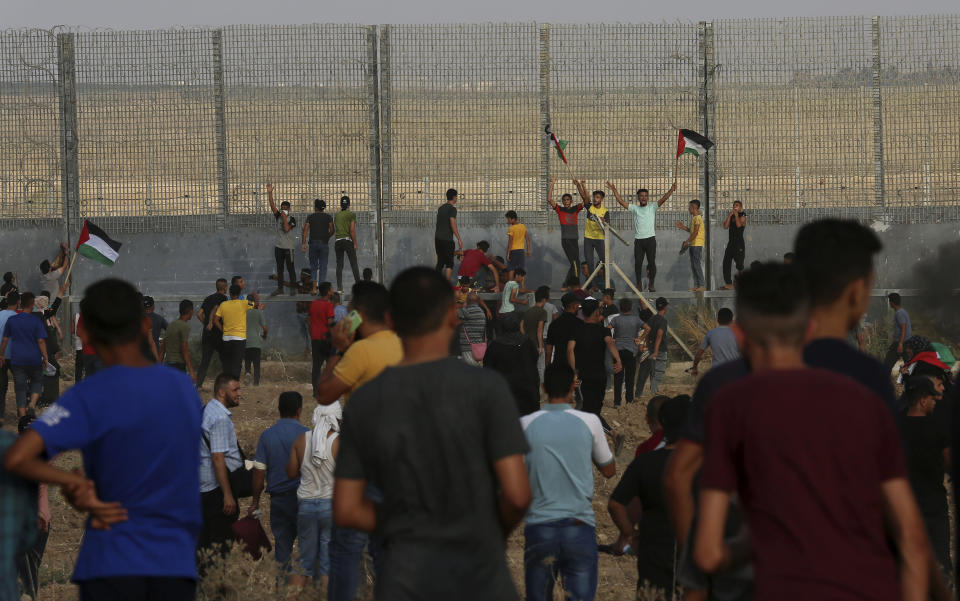 Protestors chant while try to climb the fence of the Gaza Strip's border with Israel, during a protest marking the anniversary of a 1969 arson attack at Jerusalem's Al-Aqsa mosque by an Australian tourist later found to be mentally ill, east of Gaza City, Saturday, Aug. 21, 2021. (AP Photo/Adel Hana)