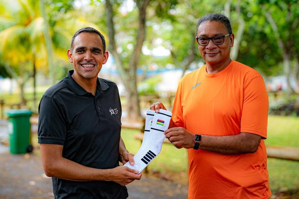 United Through Sport's Darren Taylor hands over a pair of sports socks embroidered with the Mauritian flag to Minister of Youth Empowerment, Sports and Recreation Stephan Toussaint (Ben Birchall/PA) (PA Wire)