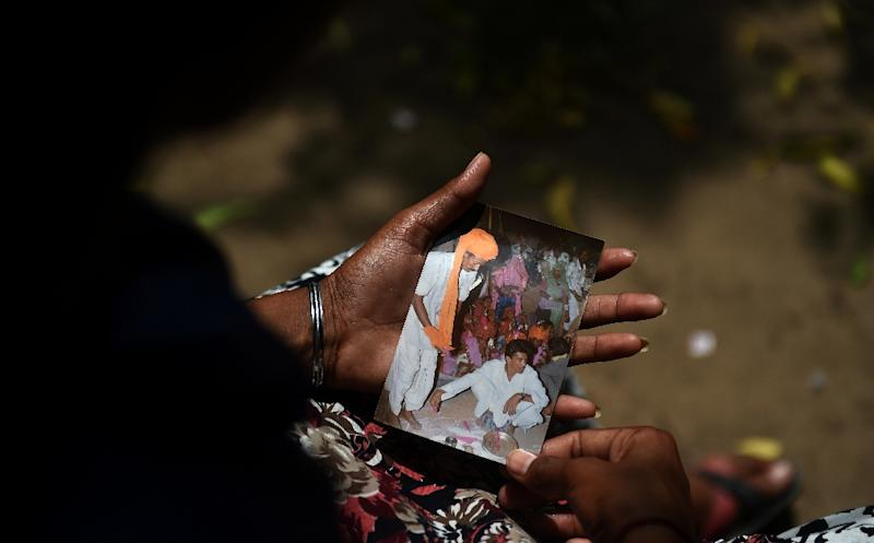 University student Santadevi Meghwal, a victim of child marriage, looks at a photograph of her wedding ceremony in Jodhpur (AFP Photo/Money Sharma)