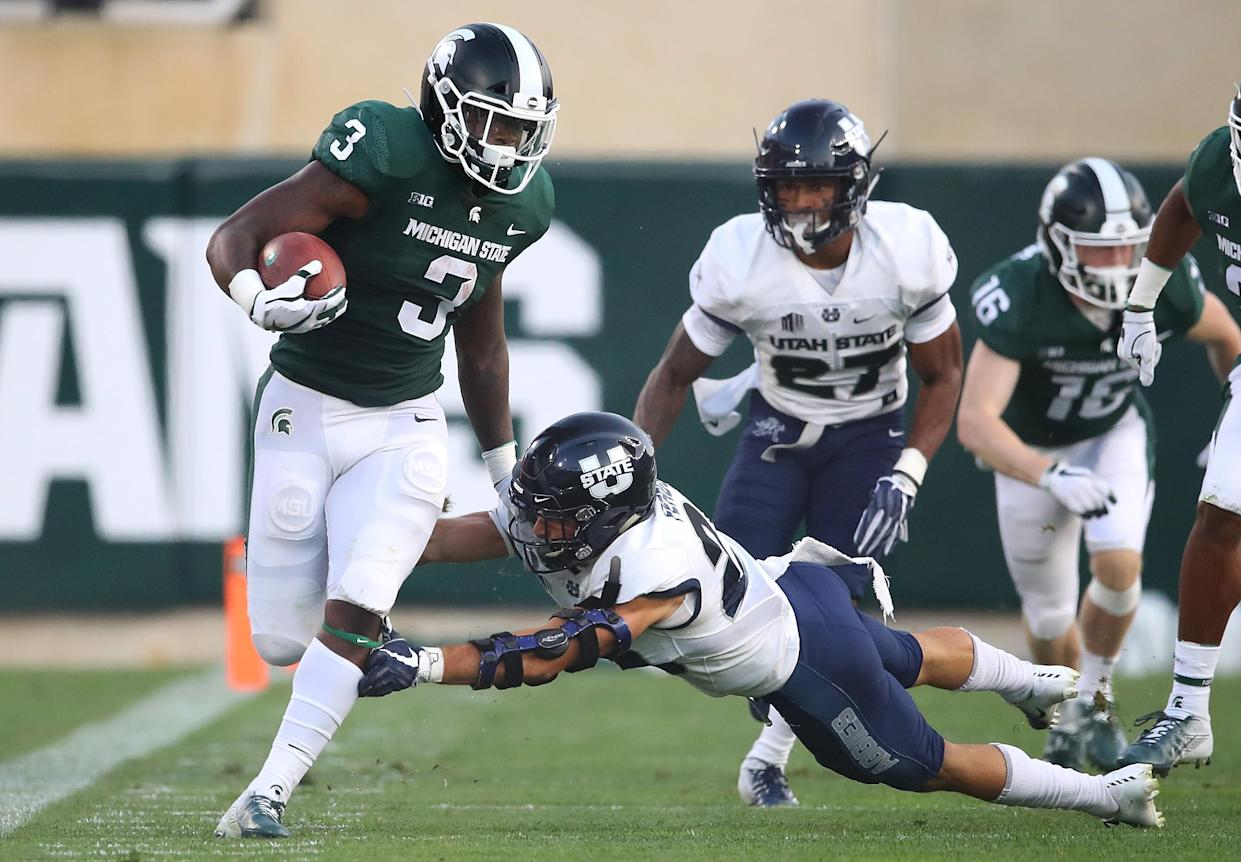 """EAST LANSING, MI – AUGUST 31: LJ Scott #3 of the Michigan State Spartans tries to run through the tackle of Gaje Ferguson #23 of the <a class=""""link rapid-noclick-resp"""" href=""""/ncaaf/teams/uud"""" data-ylk=""""slk:Utah State Aggies"""">Utah State Aggies</a> at Spartan Stadium on August 31, 2018 in East Lansing, Michigan. (Photo by Gregory Shamus/Getty Images)"""