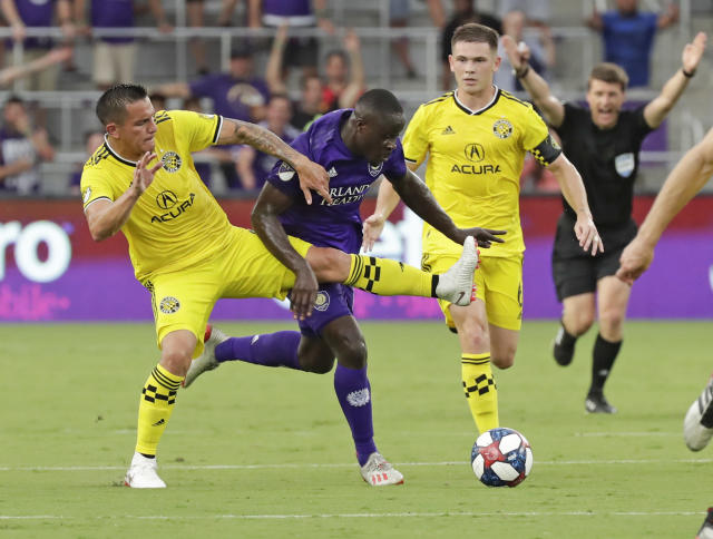 Columbus Crew's David Guzman, left, tries to move the ball past Orlando City's Benji Michel as Will Trapp, right, watches during the first half of an MLS soccer match Saturday, July 13, 2019, in Orlando, Fla. (AP Photo/John Raoux)