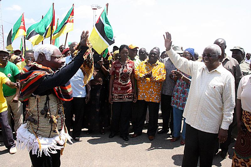 President of Mozambique Armando Guebuza (R) greets supporters on his arrival in Chimoio on October 30, 2013
