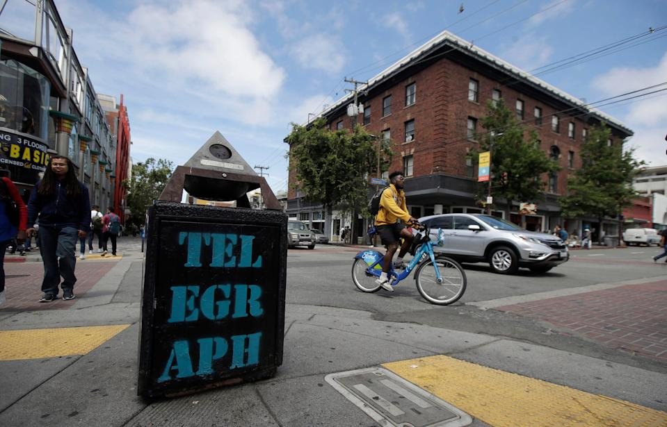 In this July 18, 2019, file photo, traffic and pedestrians cross Telegraph Avenue in Berkeley, California. The politically liberal city of Berkeley in Northern California decided last year to shift traffic enforcement from armed police to unarmed city workers. Supporters said the separation would curb racial profiling and reduce police encounters that can turn deadly, especially for Black motorists.