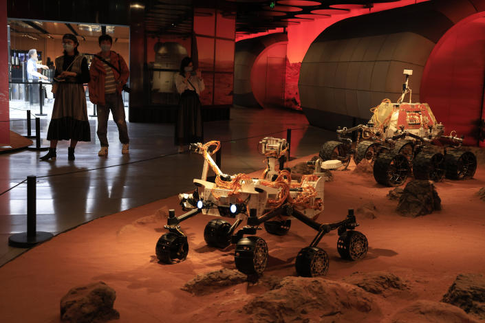 Visitors pass by an exhibition depicting rovers on Mars in Beijing on Friday, May 14, 2021. China says its Mars probe and accompanying rover are to land on the red planet sometime between early Saturday morning and Wednesday Beijing time. (AP Photo/Ng Han Guan)