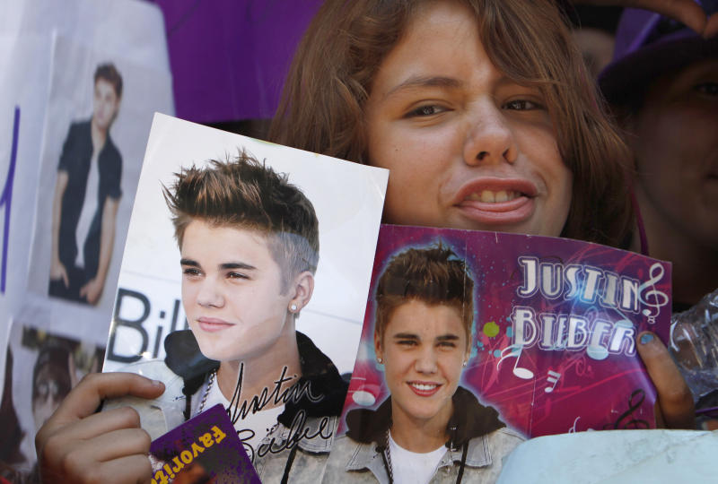 A fan holds images of pop starJustin Bieber in Mexico City's main historic plaza, the Zocalo, Sunday, June 10, 2012. The Beliebers have arrived in the chaotic streets of Mexico City, adolescents in purple and white and braving two nights on roach-infested sidewalks for a chance to be closest to the stage when teenage superstar Justin Bieber puts on a free concert Monday evening on the capital's vast central plaza. (AP Photo/Marco Ugarte)