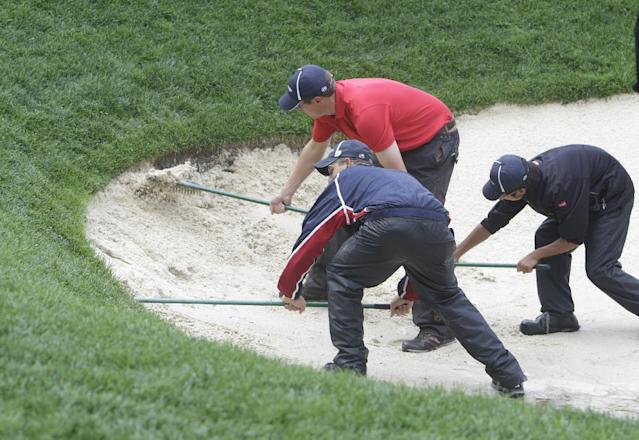 Groundskeepers rake a bunker on the 15th during a rain delay in the four-ball matches at the Presidents Cup golf tournament at Muirfield Village Golf Club Saturday, Oct. 5, 2013, in Dublin, Ohio. (AP Photo/Jay LaPrete)