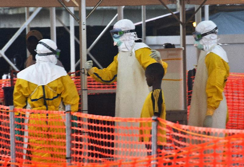 Health workers with a patient under quarantine at the Nongo Ebola treatment centre in Conakry, Guinea on August 21, 2015