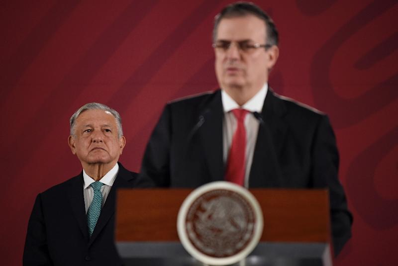 Mexican President Andres Manuel Lopez Obrador (L) listens to Foreign Minister Marcelo Ebrard during a press conference in Mexico City on an immigration deal with the US