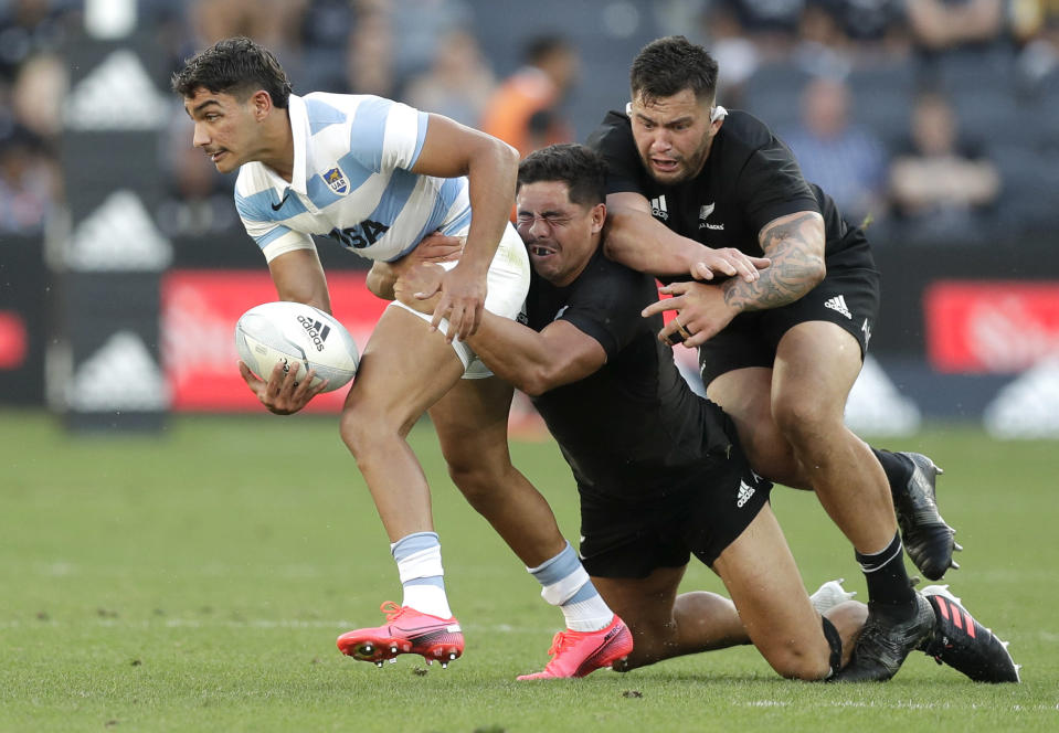 Argentina's Santiago Carreras, left, is tackled by New Zealand's Anton Lienert-Brown, centre, and Tyrel Lomax, right, during the Tri-Nations rugby test between Argentina and New Zealand at Bankwest Stadium, Sydney, Australia, Saturday, Nov.14, 2020. (AP Photo/Rick Rycroft)