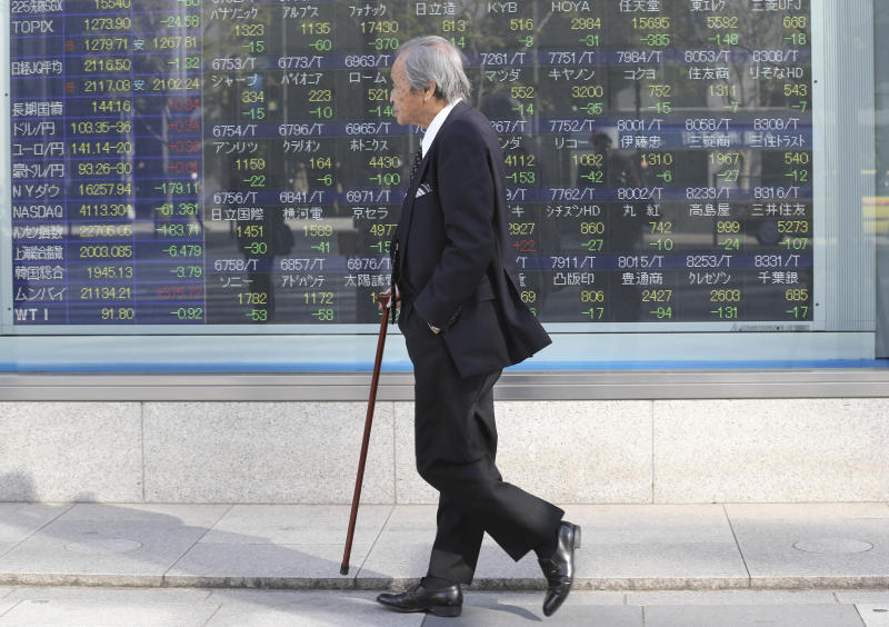 A man walks by an electronic stock board of a securities firm in Tokyo, Tuesday, Jan. 14, 2014. Most Asian stock markets sank Tuesday, led by Japan, following a big sell-off in the U.S.(AP Photo/Koji Sasahara)