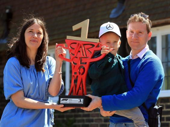 Five-year-old Harry holds Hamilton's Spanish Grand Prix trophy (PA)