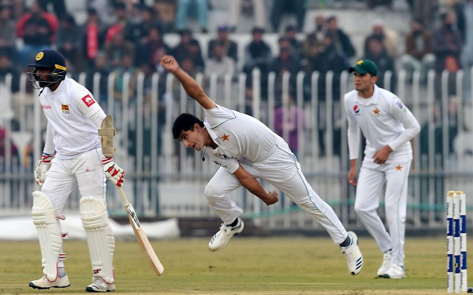 Pakistan's Naseem Shah (C) delivers a ball next to Sri Lanka's Dilruwan Perera (L) as Pakistan's Shaheen Shah Afridi (R) looks on during the third day of the first Test cricket match between Pakistan and Sri Lanka at the Rawalpindi Cricket Stadium - AAMIR QURESHI / AFP