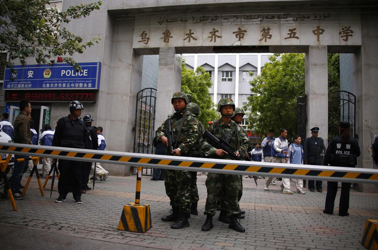 Paramilitary policemen stand guard in front of Urumqi No. 5 middle school after Thursday's attack in downtown Urumqi, Xinjiang Uighur Autonomous Region May 23, 2014. Five suicide bombers carried out the attack which killed 31 people in the capital of China's troubled Xinjiang region, state media reported a day after the deadliest terrorist attack to date in the region. REUTERS/Petar Kujundzic (CHINA - Tags: MILITARY CIVIL UNREST CRIME LAW EDUCATION TPX IMAGES OF THE DAY)