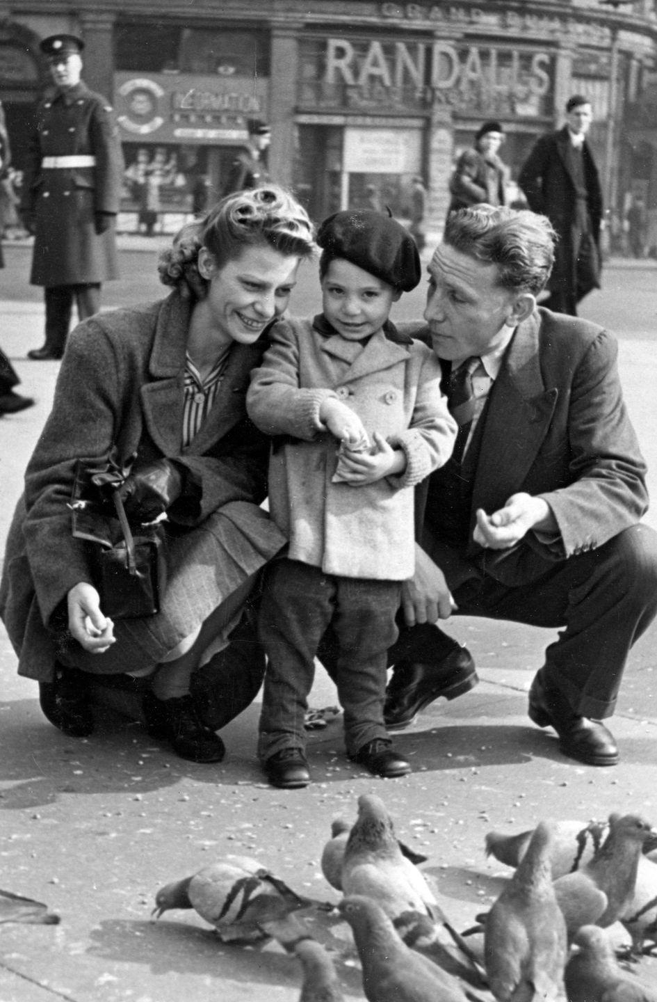 <p>Charles Robert Watts aged 2 with his mother Lillian and father Charles in Piccadilly Circus in 1943.</p>