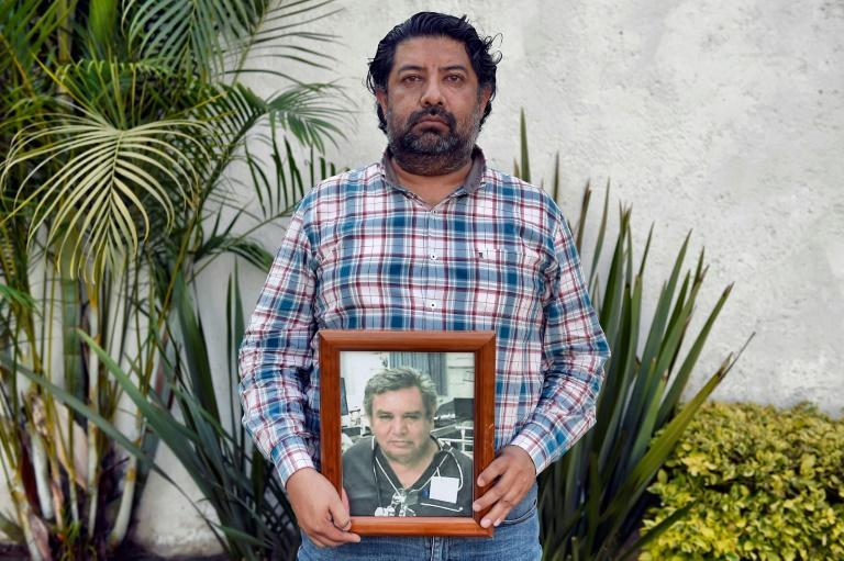 Federico de la Torre holds a picture of his late father Jesus de la Torre, an emergency physician who died from the coronavirus