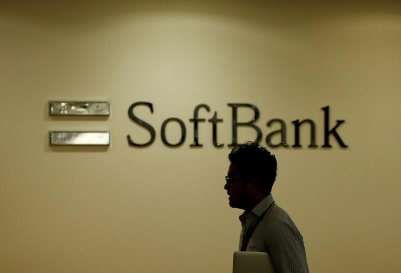 Man walks past the logo of SoftBank Group Corp at the company's headquarters in Tokyo