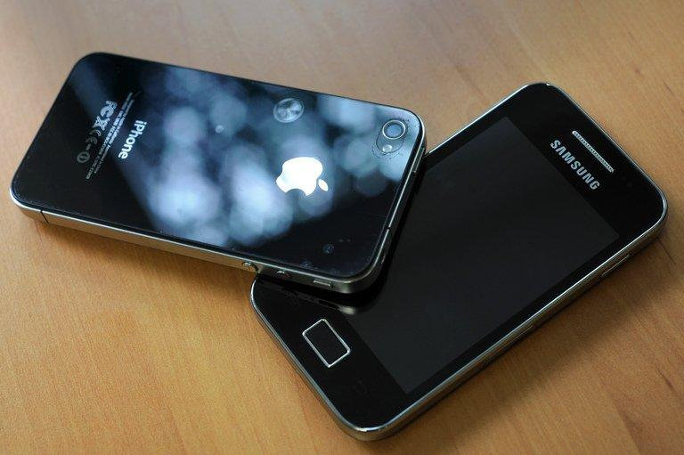 A picture taken on October 12, 2011 in the French western city of Rennes shows a Samsung phone (R) and an iPhone 4