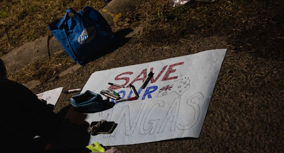 Someone painting a protest sign saying Save Our Kangas.