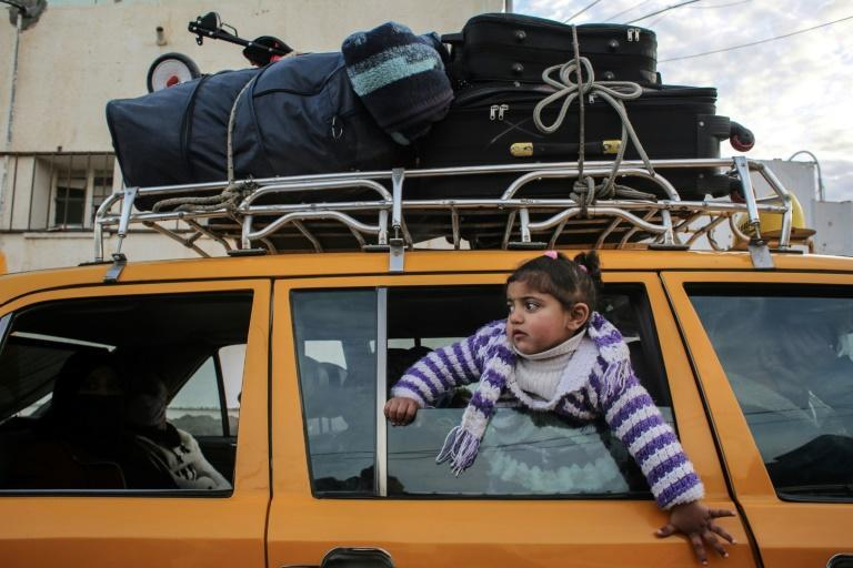 A girl pokes her head through the window of a loaded vehicle at the Rafah border crossing between Gaza and Egypt