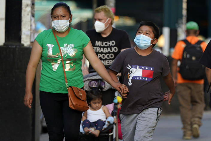 FILE — In this May 19, 2021 file photo. pedestrians wear protective masks during the coronavirus pandemic, in the Queens borough of New York. New York Gov. Andrew Cuomo and New York City Mayor Bill de Blasio have scheduled competing news conferences Monday, Aug. 2 amid rising COVID-19 case counts attributed to the highly contagious delta variant of the virus. (AP Photo/Frank Franklin II, File)