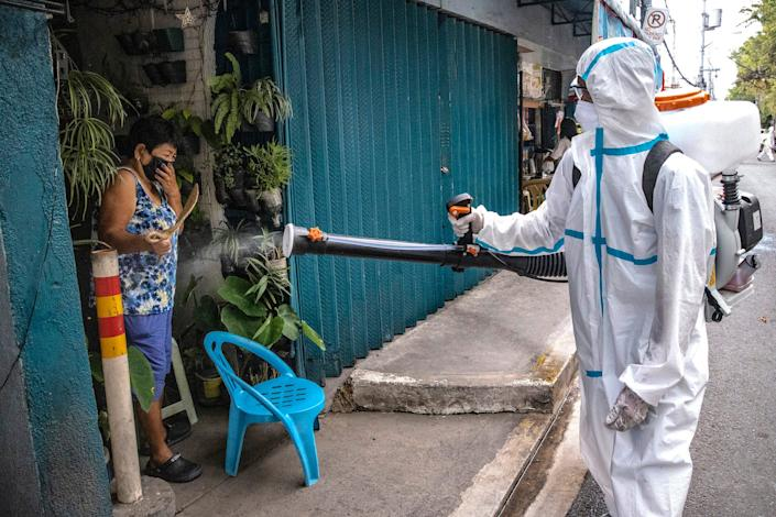 A woman reacts as a disinfection worker sprays disinfectant along a street at a suburban area on March 23, 2020 in San Juan, Metro Manila, Philippines.