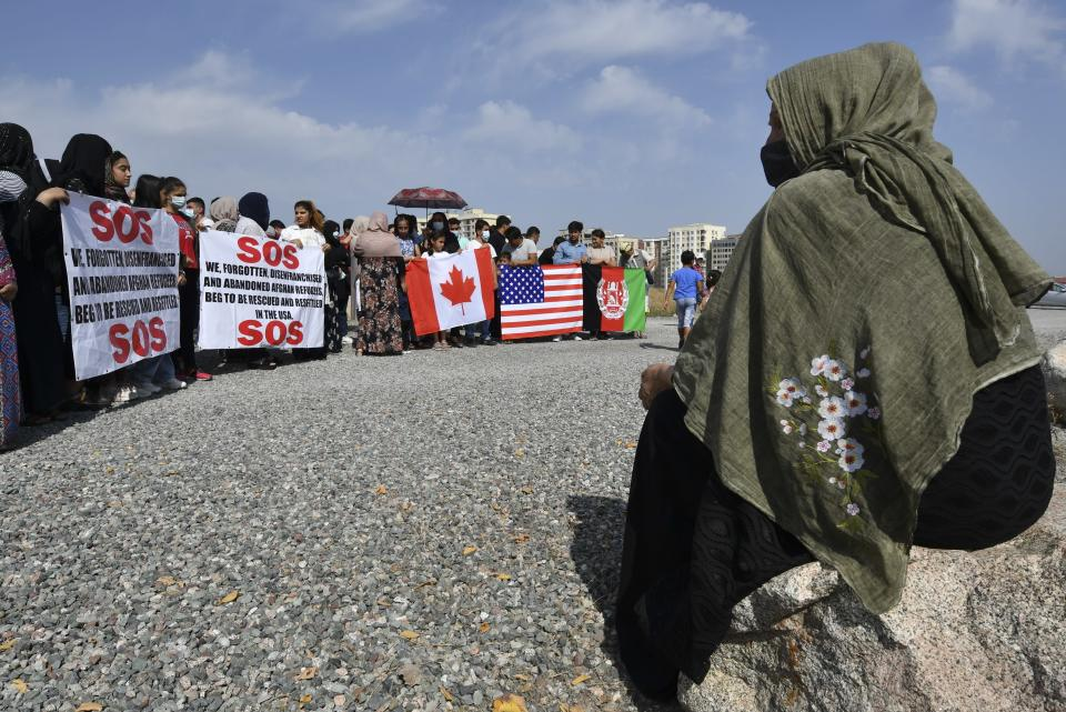 Afghans migrants take part in a rally outside the U.S. Embassy in Bishkek, Kyrgyzstan, Thursday, Aug. 19, 2021, requesting Kyrgyz citizenship or resettlement to the USA or Canada. (AP Photo/Vladimir Voronin)