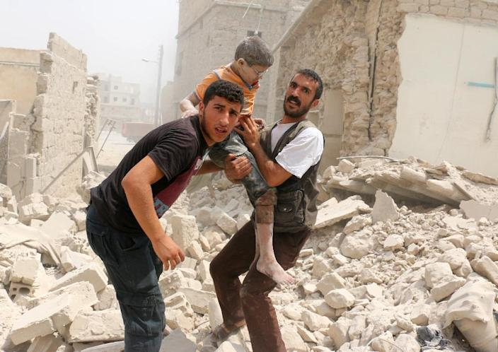 Syrians carry a wounded child in the rubble of buildings following a barrel bomb attack on the Bab al-Nairab neighbourhood of the northern Syrian city of Aleppo on August 25, 2016 (AFP Photo/Ameer Alhalbi)