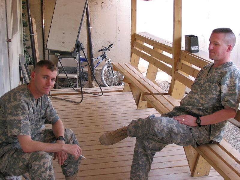 """This 2007 photo provided by Brock McNabb shows Pete Linnerooth, right, and Travis Landchild sitting outside their mental health clinic in Baghdad. McNabb, Landchild and Linnerooth were the tight-knit mental health crew in charge of the 2nd Brigade Combat Team, 1st Infantry Division in the Baghdad area. They were there when the surge began, rocket attacks increased and the death toll mounted. Fairchild says the three dubbed themselves """"a dysfunctional tripod."""" Translation: One of the three 'legs' was always broken, or stressed out, and without fail, """"the other two would step up and support that person."""" (AP Photo/Brock McNabb)"""